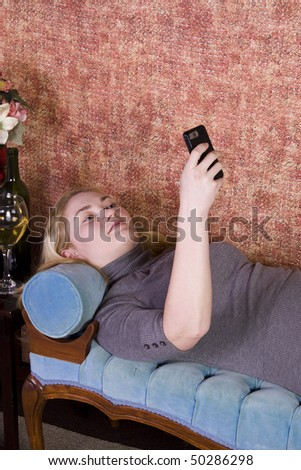Teenager Talking on the Cell Phone on a Green Couch - stock photo