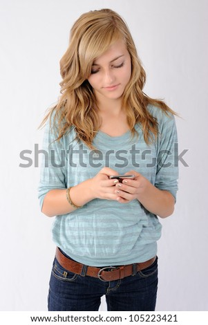 Teenager Texting on Smartphone. Thirteen year old girl looking at her smartphone while texting. Note: Not Isolated. - stock photo