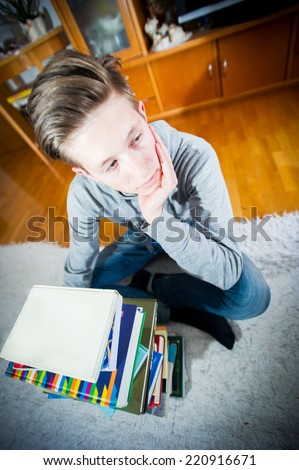 Teenager thinking in front of a stack of books.