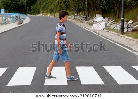 Teenager through a zebra crossing in his town - stock photo