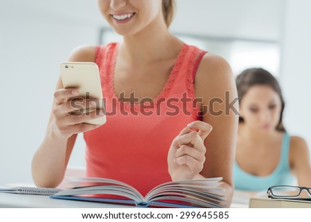 Teenager using her mobile phone in the classroom and text messaging, she is sitting at school desk with an open book - stock photo