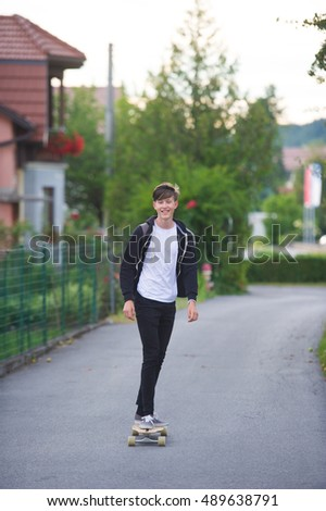 Teenager  using his longboard on a suburban street.
