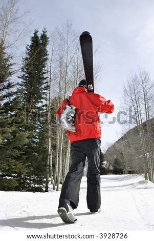 Teenager walking and carrying ski gear. - stock photo