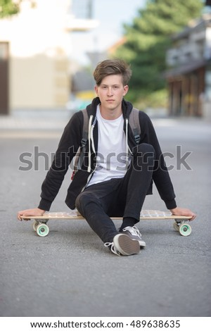 Teenager wearing backpack sitting casually on a longboard.