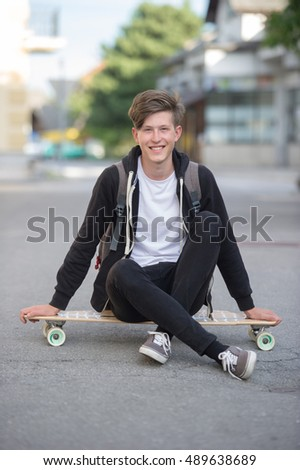Teenager wearing backpack sitting casually on a longboard and smiling.