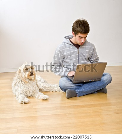 teenager with a laptop computer and his dog on a parquet floor - stock photo