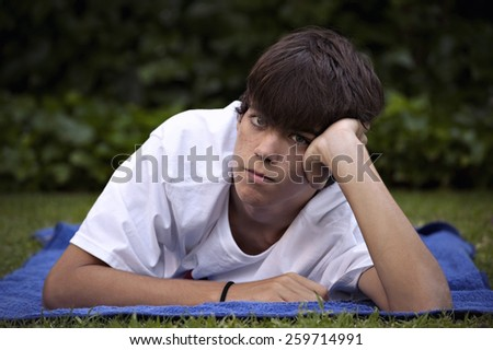 Teenager, with acne knocked down in the grass - stock photo