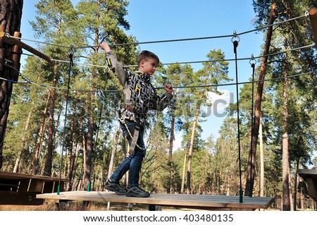 teenager with equipment on ropes in amusement park