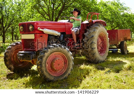 Teenager with hat driving an old tractor with trailer through an orchard