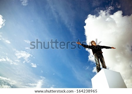 Teenager with his arms wide open looking into a blue sky - stock photo