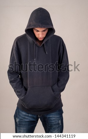 teenager with hoodie looking down against a dirty gray wall - stock photo