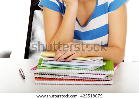 Teenager with huge heap of copybooks - stock photo