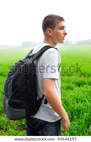 teenager with knapsack in the summer field