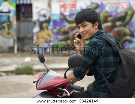 Teenager with mobile telephone sitting on motorbike - stock photo