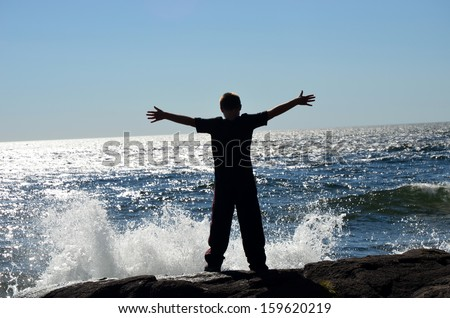 teenager with outspread arms being hit by large waves of water