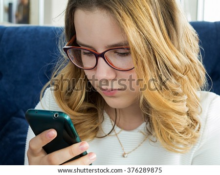 teenager with poor eyesight looking at mobile phone