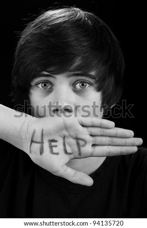Teenager with scared look needing help - on black background - stock photo