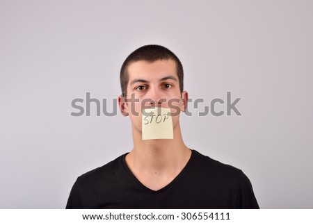 teenager with stop note on his mouth - stock photo