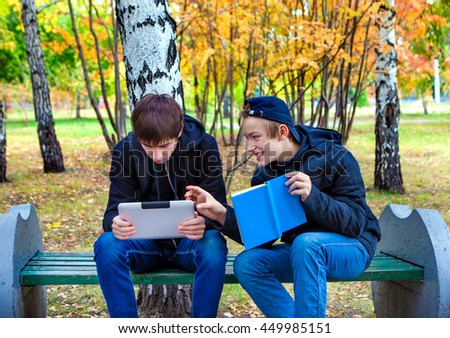 Teenager with Tablet Computer and Kid with the Book in the Autumn Park