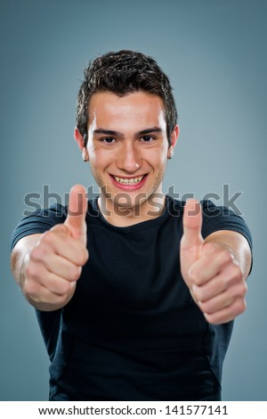Teenager with Thumbs Up Over a Grey Background  - stock photo