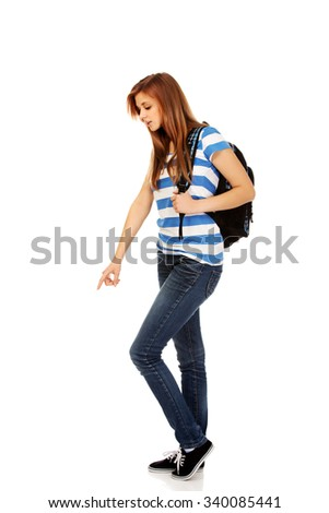 Teenager woman with backpack pointing for soomething.