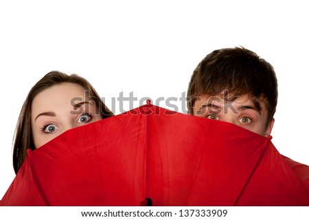 Teenagers, a boy and a girl, peeping for the red umbrella.  Isolated on white background. - stock photo