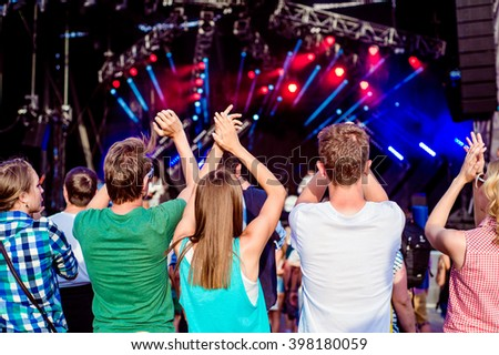 Teenagers at summer music festival clapping and singing - stock photo