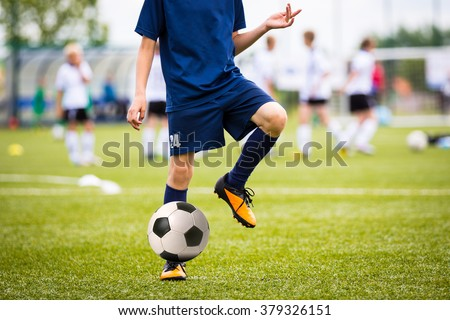 Teenagers Boys Playing Soccer Football Match. Young Football Players Running and Kicking Soccer Ball on a Soccer Pitch. - stock photo