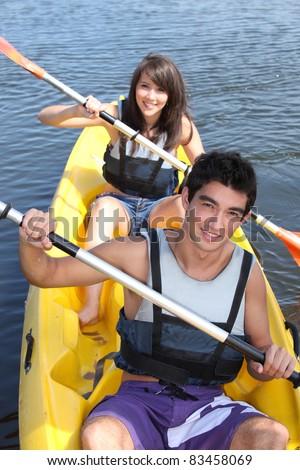 Teenagers canoeing - stock photo