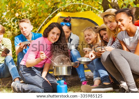 Teenagers cook soup in metallic pot during camping