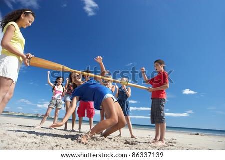 Teenagers doing limbo dance on beach - stock photo