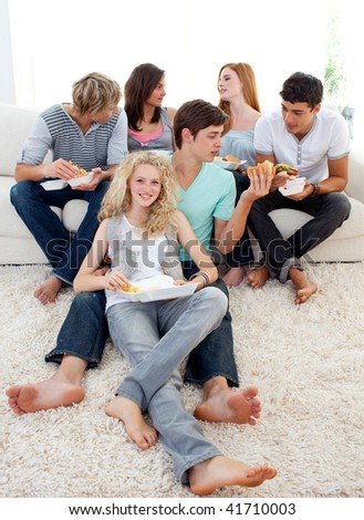 Teenagers eating burgers and fries on the sofa - stock photo