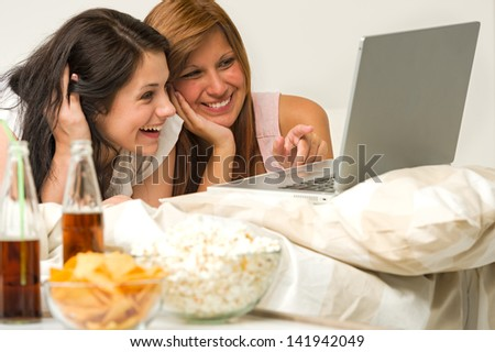 Teenagers friends enjoy movie night watching laptop and laughing - stock photo
