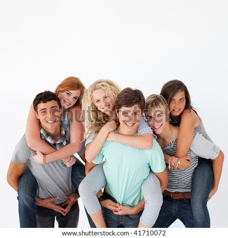 teenagers giving their friends piggyback rides against white background - stock photo