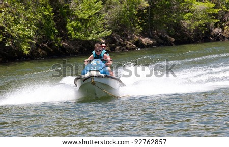 Teenagers go for a drive on the scooter on the river - stock photo