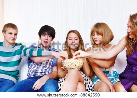 Teenagers group eating popcorn together - stock photo