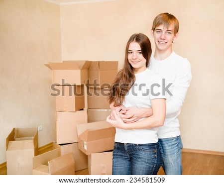 Teenagers hugging on a background of cardboard boxes