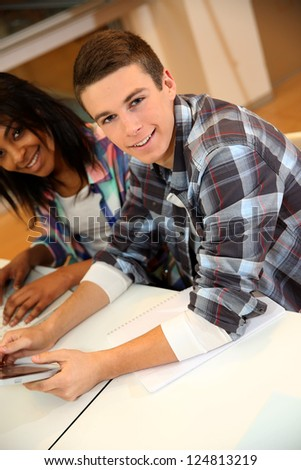 Teenagers in class using electronic tablet - stock photo