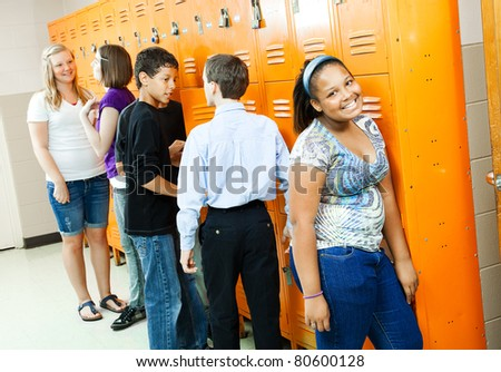 Teenagers in the hallway, at their lockers between classes. - stock photo