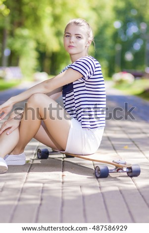 Teenagers Lifestyle, Concepts and Ideas. Blond Caucasian Girl Posing With Longboard in Park Outdoors. Vertical Shot
