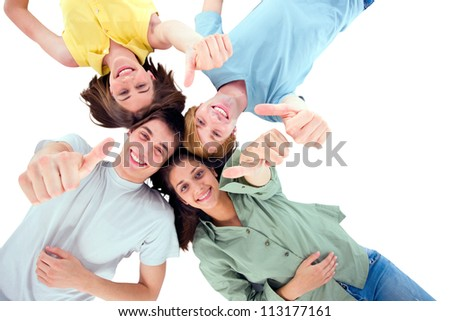 teenagers lying down with thumbs up - stock photo