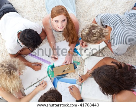 Teenagers lying on the ground studying together - stock photo