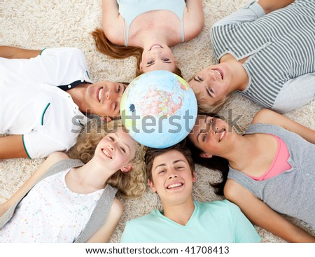 Teenagers on the floor with a terrestrial globe in the center of their heads - stock photo