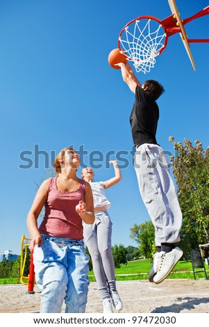 Teenagers playing basketball in a city park - stock photo