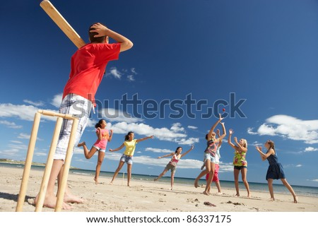 Teenagers playing cricket on beach - stock photo