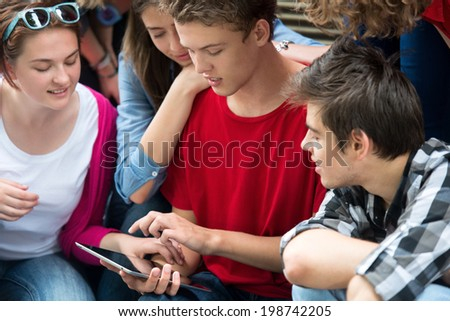 Teenagers playing games on a tablet computer