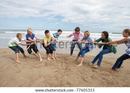 Teenagers playing tug of war - stock photo