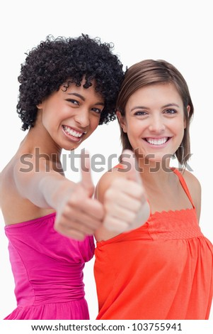 Teenagers proudly putting their thumbs up against a white background - stock photo