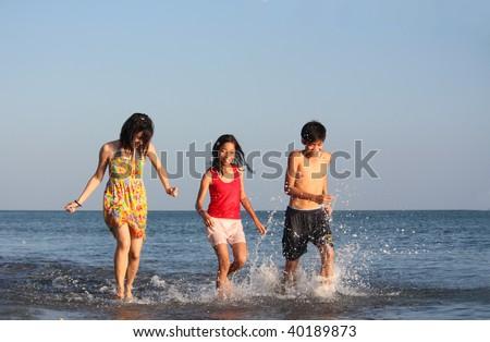 teenagers running along the beach - stock photo