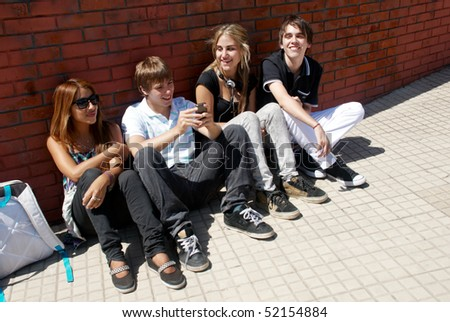 Teenagers Sitting by a street